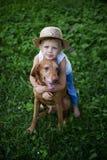 Kamratskap mellan ett barn och en hund Arkivbilder