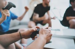 Kamratskap, teknologi, lekar och hemmastatt begrepp för avslappnande tid - som är nära upp av manliga vänner som spelar videospel royaltyfri foto