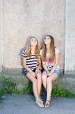 Kamratskap - två bästa flickvänner mot grå bakgrund Arkivbilder