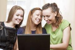 Kamratskapbegrepp: Tre skratta Caucasian flickor som använder bärbara datorn Royaltyfri Bild
