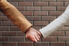Kamratskaphjälpförtroende förbinder handen för enhetbffhållen arkivbild