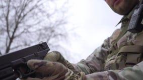 Kamuflaż jest ubranym żołnierza dostaje automatyczną krócicę z holster zdjęcie wideo