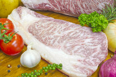 Kamui Wagyu牛肉高大理石小条腰部切开了成片断 安置在有菜的木板材 免版税图库摄影