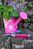 kan arbeta i trädgården att bevattna Arkivfoto