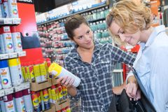 Kan de winkel hulpholding verf bespuiten stock foto