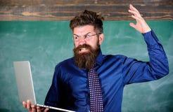 Kan inte få van vid modern teknologi Läraren uppsökte mannen med modern svart tavlabakgrund för bärbara datorn Hipsterlärare royaltyfria bilder