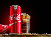 Kan och exponeringsglas av cocaen - cola med is på träbakgrund Royaltyfria Bilder