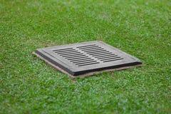 Kanał ściekowy kratownica na gazonie - drenaż dla ulewnego deszczu zdjęcie royalty free