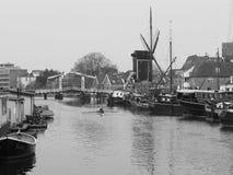 Kanał z łodziami i wiatraczkiem przy chmurnym dniem w Leiden Fotografia Royalty Free