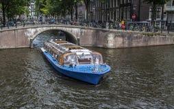 Kanałowa łódź pokazuje turystów wokoło Amsterdam Fotografia Stock