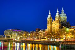 Kanaal en St Nicholas Church in Amsterdam bij schemering, Nederland Het beroemde oriëntatiepunt van Amsterdam dichtbij Centrale P royalty-vrije stock afbeelding