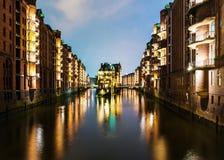 Kanaal in het midden van verlichte gebouwen in oud pakhuisdistrict Speicherstadt in Hamburg bij nacht Stock Afbeelding