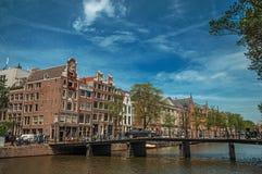 Kanaal met baksteengebouwen, fietsen op brug en zonnige blauwe hemel in Amsterdam Royalty-vrije Stock Foto
