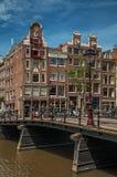 Kanaal met baksteengebouwen, fietsen op brug en zonnige blauwe hemel in Amsterdam Stock Foto's