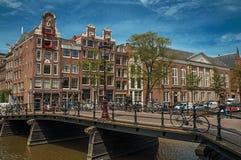 Kanaal met baksteengebouwen, fietsen op brug en zonnige blauwe hemel in Amsterdam Stock Fotografie