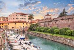 Kanaal met boten en muren van de oude vesting in Livorno, Tusca Stock Foto's