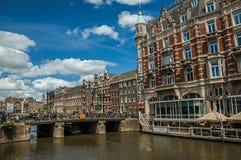 Kanaal met typische baksteengebouwen, mensen over brug en blauwe hemel in Amsterdam royalty-vrije stock afbeelding