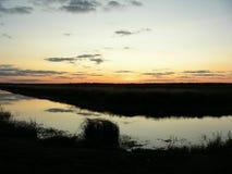 Kanaal met water op het gebied, in de weide na zonsondergang royalty-vrije stock fotografie