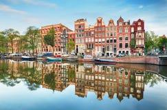 Kanaalhuizen van Amsterdam bij schemer met trillende bezinningen, Neth stock afbeeldingen