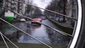 Kanaalschipzeil op smal kanaal in Amsterdam fietswiel in de voorgrond stock footage