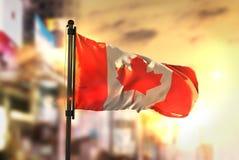 Kanada flagga mot suddig bakgrund för stad på soluppgångpanelljuset Royaltyfri Bild