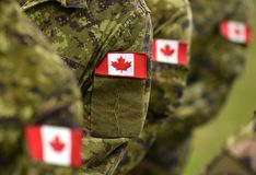 Kanada lappflaggor på soldatarmen Kanadensiska soldater royaltyfri fotografi