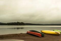 Kanada Ontario kanoter för kanoten för atmosfär för den gråa morgonen för floder för sjö två sätter på land parkerade mörka vatte arkivbild