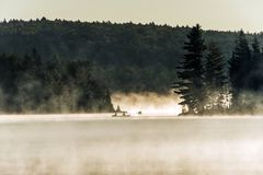 Kanada Ontario sjön av två floder kanotar för vattensoluppgång för kanoter den guld- timmen för dimmig dimma på vatten i Algonqui royaltyfri bild