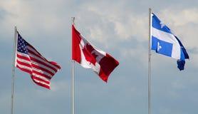 Kanada, usa i Quebec flaga macha w wiatrowym chmurnym dniu, obraz stock