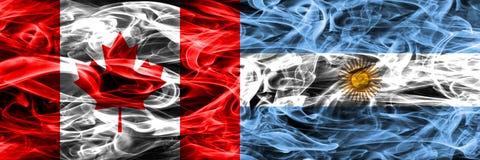 Kanada vs Argentyna dymu flaga umieszczająca strona strona - obok - Kanadyjczyk zdjęcia royalty free