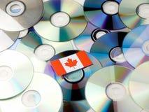 Kanadensisk flagga överst av CD- och DVD-högen som isoleras på vit arkivfoton
