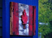 Kanadensisk flagga som göras ut ur trä som hänger på en träladugårddörr fotografering för bildbyråer