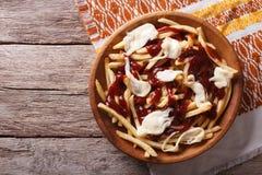 Kanadensisk kokkonst: poutine med sås och ost horisontalöverkant Royaltyfri Foto
