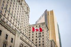 Kanadische Flagge vor einem Geschäftsgebäude und ein älterer Wolkenkratzer in Toronto, Ontario, Kanada lizenzfreie stockfotos