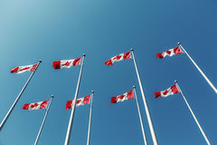 Kanadische Flaggen, die über blauen Himmel wellenartig bewegen Lizenzfreie Stockbilder