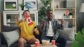 Kanadische Sportfans der jungen Leute passen Spiel, im Fernsehen auf die Flaggen von Kanada wellenartig zu bewegen positive Gefüh stock footage