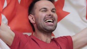 Kanadischer feiernder Fan beim Halten der Flagge von Kanada stock footage