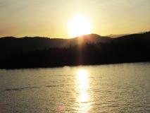 Kanadischer Sonnenuntergang hinter den Bergen, die auf Ozean glitzern stockfotografie