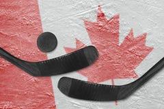 Kanadyjczyk flaga i dwa hokejowego kija hokejowych zdjęcia royalty free