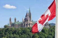 Kanadyjczyka chorągwiany falowanie z parlamentów budynkami obrazy stock