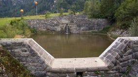 Kanal av det lilla dammet för vattenbarriärer på fjällängar arkivfoton