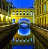 Kanal av floden som lämnar i en båge med reflexion i vatten bland väggar av byggnader på varje sida, St Petersburg, eremitboning royaltyfri foto