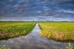 Kanal i holländsk jordbruksmark med reflekterad himmel fotografering för bildbyråer