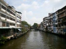 Kanal längs gamla hus med den järnväg korsningen flod Arkivbild