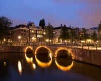 Kanal med bron i Amsterdam på natten arkivbild