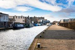 Kanal med förtöjde fartyg och en kullerstenkaj royaltyfria foton