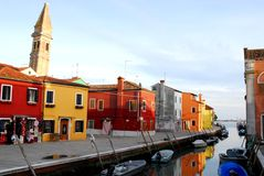 Kanal med fartyg, färgrika hus och klockatornet i Burano Venedig område Italien Arkivbild