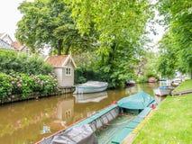 Kanal med fartyg i gammal stad av Broek i Waterland, Nederländerna royaltyfria bilder