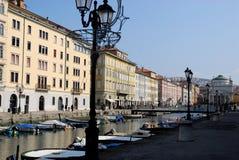 Kanal med fartyg, lyktstolpar och byggnader under den blåa himlen i Trieste i Friuli Venezia Giulia (Italien) arkivfoto
