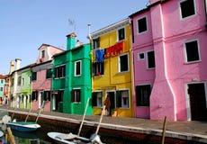 Kanal med fartyg och färgrika hus i Burano i Venedig i Italien Royaltyfri Bild